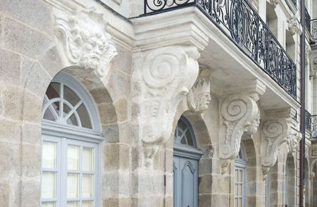 Architectural sculptures - mascarons - on the facade of a 18th century building in Nantes, France. Black wrought iron balcony and corbels on tuffeau stone facade.