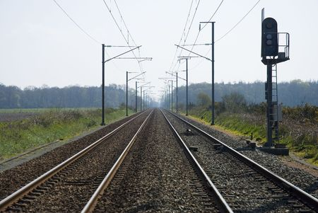 Railway shot with overhear cables and side lights. Centered vanishing point perspective