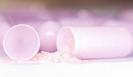 Extreme close-up of an opened pink capsule filled and poured pink powder. Stock Photo
