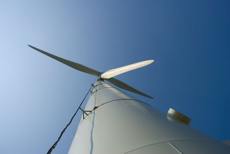 Looking up at a three-bladed wind turbine. Low angle shot.