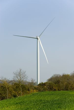 Vertical view of an horizontal axis three-bladed wind turbine on a green field.