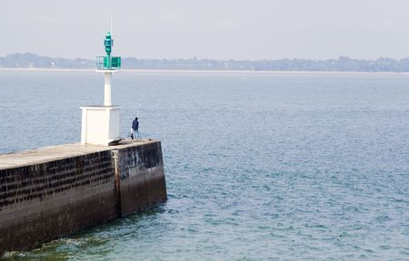 Man fishing from a pier, near a small headlight Stock Photo - 970146