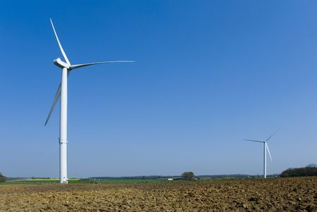 Two wind turbines in country. Empty space for free text in upper right corner on blue sky background.