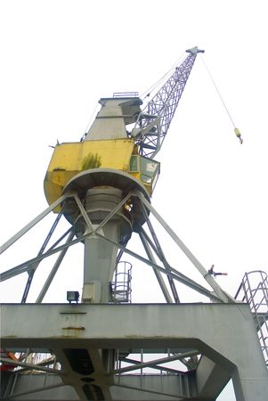 Harbour crane from below against white sky background