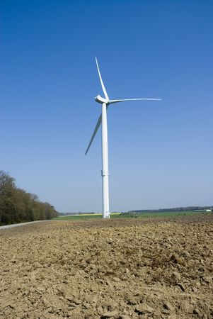 Wind Turbine with soil in foreground. Vertical view. Stock Photo