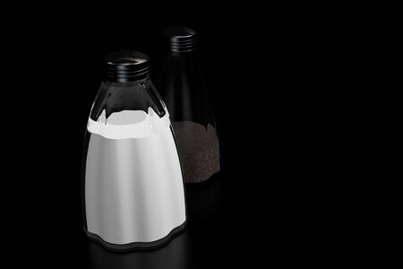 Salt and pepper shakers on a black reflective background Stock Photo