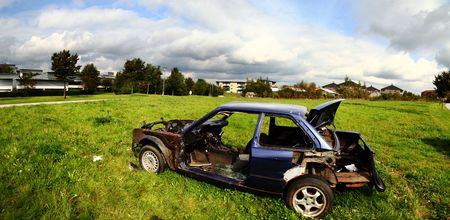 trashed: Car stolen and wrecked. panoramic of vehicle burned out on housing estate Stock Photo