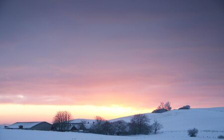 sunset over farm in the winter. landscape with snow photo