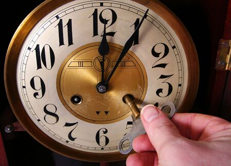 past midnight: clock, old vintage time piece in wood and brass showing just past twelve or midnight wind-up Stock Photo
