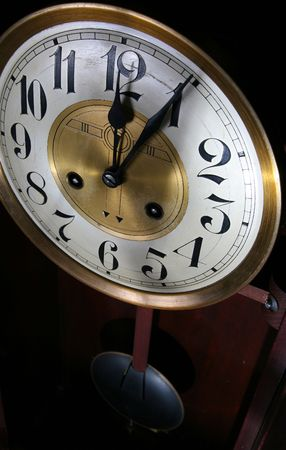 12: clock, old vintage time piece in wood and brass showing just past twelve or midnight Stock Photo
