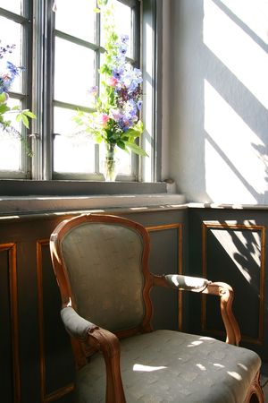 antique armchair in front of window with flowers in background in manor house photo