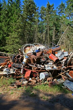 rubbish dump pollution. forest with industry metal scrap photo