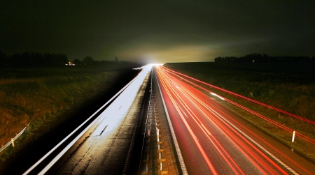 speeding: road with driving car at night with motion blur and lights. Stock Photo