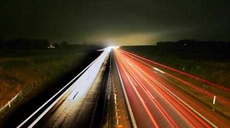 su strada con la Guida di auto di notte con luci e sfocatura di movimento. Archivio Fotografico