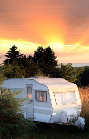roulotte in un campo dalla foresta. vecchio veicolo nel tramonto Archivio Fotografico