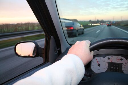 driving steering car. hand holding wheel whilst car overtaking. drive at dusk with sunset in horizon photo