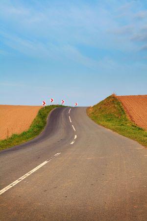 over the hill: carretera sobre la colina a trav�s de campos y tierras agr�colas. esquina o giro con se�ales de advertencia