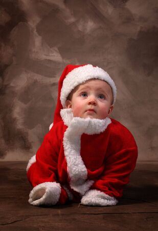 santa clause or father christmas child. baby boy in red xmas suit photo