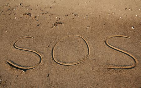 cry for help: writting in the sand on beach. Message saying sos a cry for help