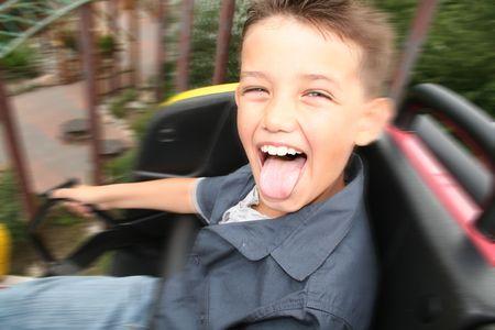 giro di montagne russe. bambino urlando con gioia nel giro del parco divertimenti