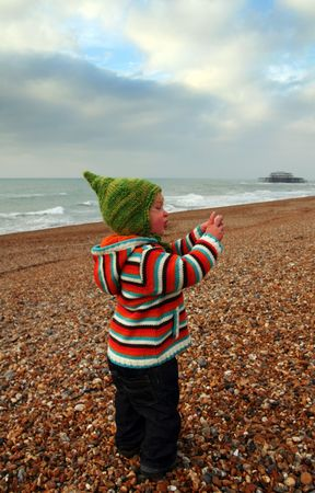 child at seaside on beach in brighton with old pier in background. holiday vacation resort in sussex in england Stock Photo - 5778935