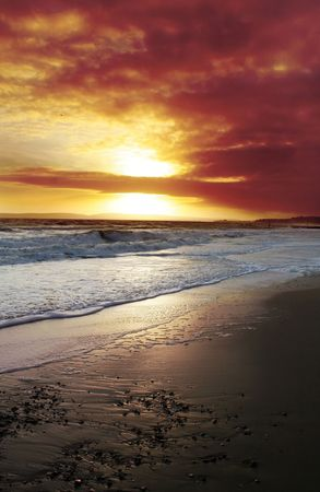 sunset over sea or ocean. waves rolling in on beach whilst sun set blood red Stock Photo - 5778076