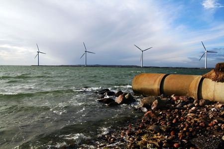 industrial park: sewage waste pipe and offshore wind mills or turbines. coast with pollution and envirnmentally friendly green energy production