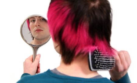brush hair and grooming whilst looking in mirror. young fashionable teenager or adult with black and pink hair photo