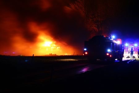 sizzle: house on fire at night. blaze of flames burn down farm  Stock Photo