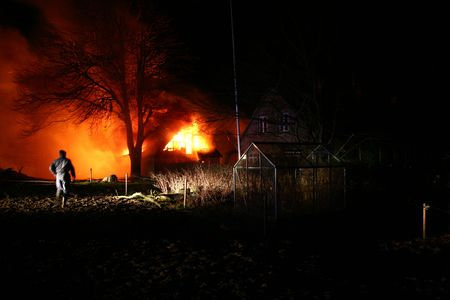 house on fire at night. blaze of flames burn down farm  Stock Photo