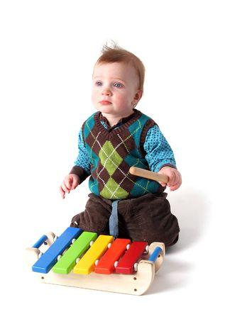 figlio di riproduzione di musica su legno xilofono strumento. toddler ragazzo con percussioni isolata on white