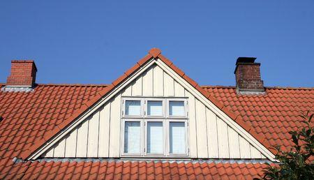 dormer: conversi�n de loft de techo o dormer. Casa de mosaico con chimeneas y ventanas contra el cielo azul  Foto de archivo