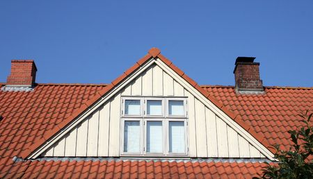 tile of roof: roof loft conversion or dormer. tiled house with chimneys and windows against blue sky Stock Photo