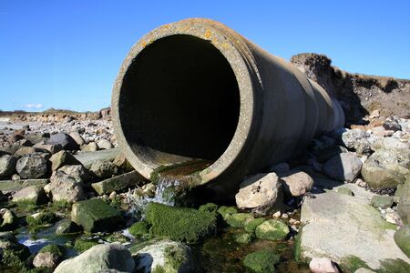 sewer pipe: waste pipe or drainage polluting environment. concrete pipes by beach