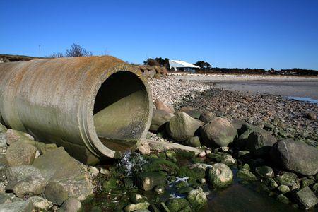 riool: afval pipe of drainage milieu vervuiling. betonnen buizen door strand  Stockfoto