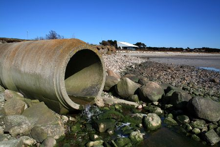 waste pipe or drainage polluting environment. concrete pipes by beach photo