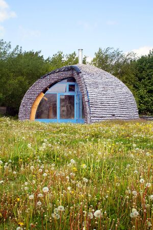 eco house made from recycle materials. environmentally friendly home in a field Stock Photo