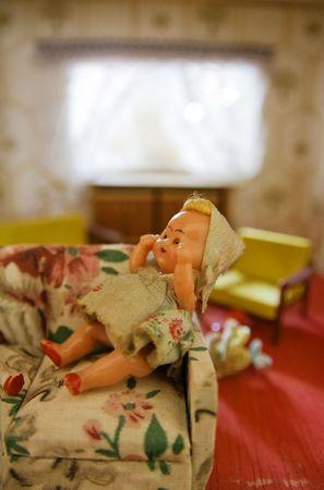 puppenhaus: Dollhouse mit Puppe im Wohnzimmer auf dem Sofa. alt antikes Childs Spielzeug