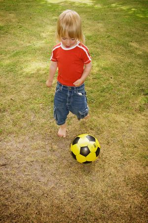 child playing football in garden. boy on field with yellow ball photo