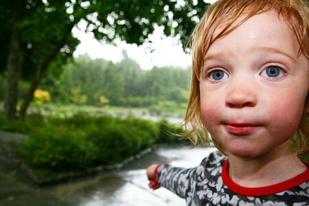 child in rain soaked with water. wet kid caught in storm in park or garden Stock Photo - 5788399