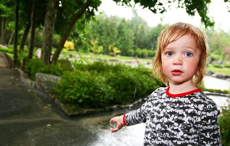 child in rain soaked with water. wet kid caught in storm in park or garden photo