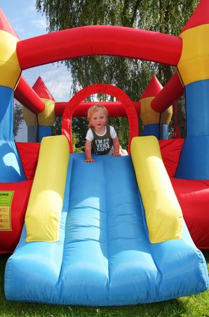 child on bouncy castle. inflatable blow-up toy for kid in garden photo