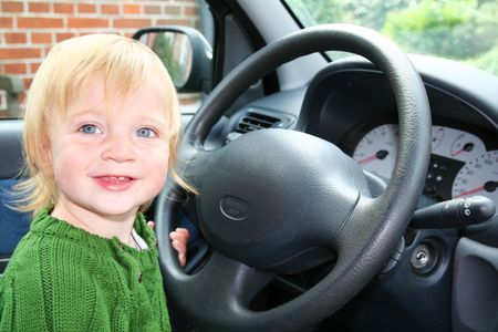 game drive: child driving car. toddler boy in vehicle holding steering wheel pretend to drive