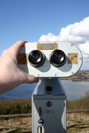 tourist spot: binoculars for pay per view. landscape wtih water and clouds. coin operated vending machine on scenic tourist spot Stock Photo