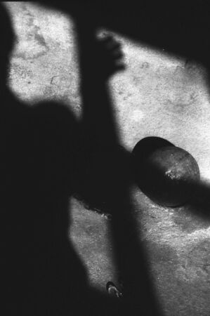 prisoner ball: infrared monchrome image of floor with shadows of figure and ball and chain
