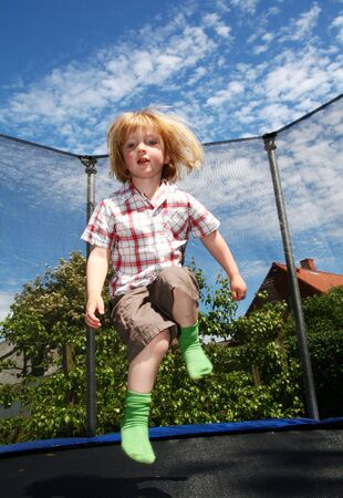 child jumping on trampoline. toddler in garden is active playing and jump photo