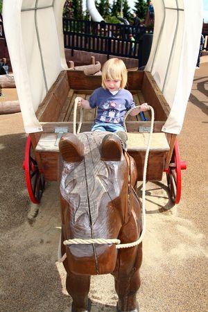 reins: child in wild west prairie wagon pretending to steer with the reins. toddler in playground