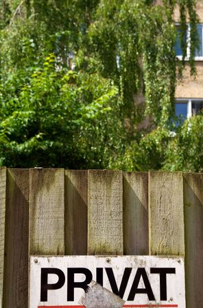 private sign on wooden fence. warning in front of building and tree Stock Photo - 5764213