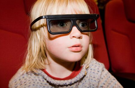 Child in 3d cinema with dark glasses on. boy watching film in movie theatre Stock Photo
