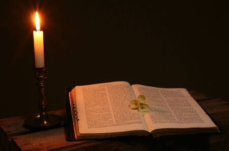 christian candle: bible on table by candle light. old christian prayer book with flowers on page